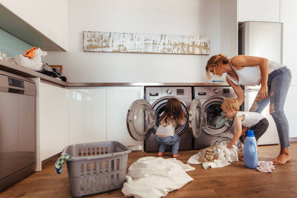 Family doing laundry together at home Woman with kids load clothes in washing machine. Mother and children putting laundry into washing machine at home. chores stock pictures, royalty-free photos & images