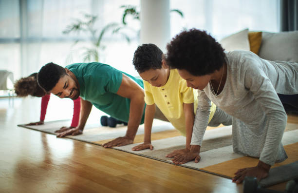Family doing pushups at home. stock photo