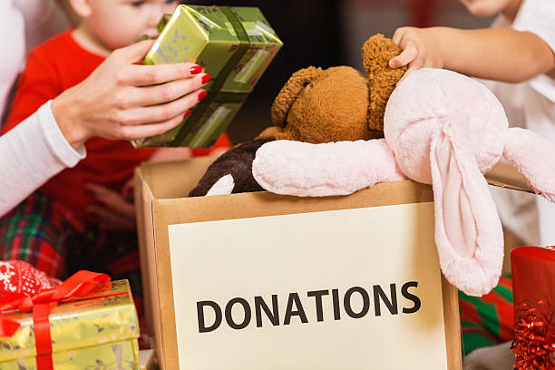 Family donating gifts and toys to charity for Christmas holiday stock photo