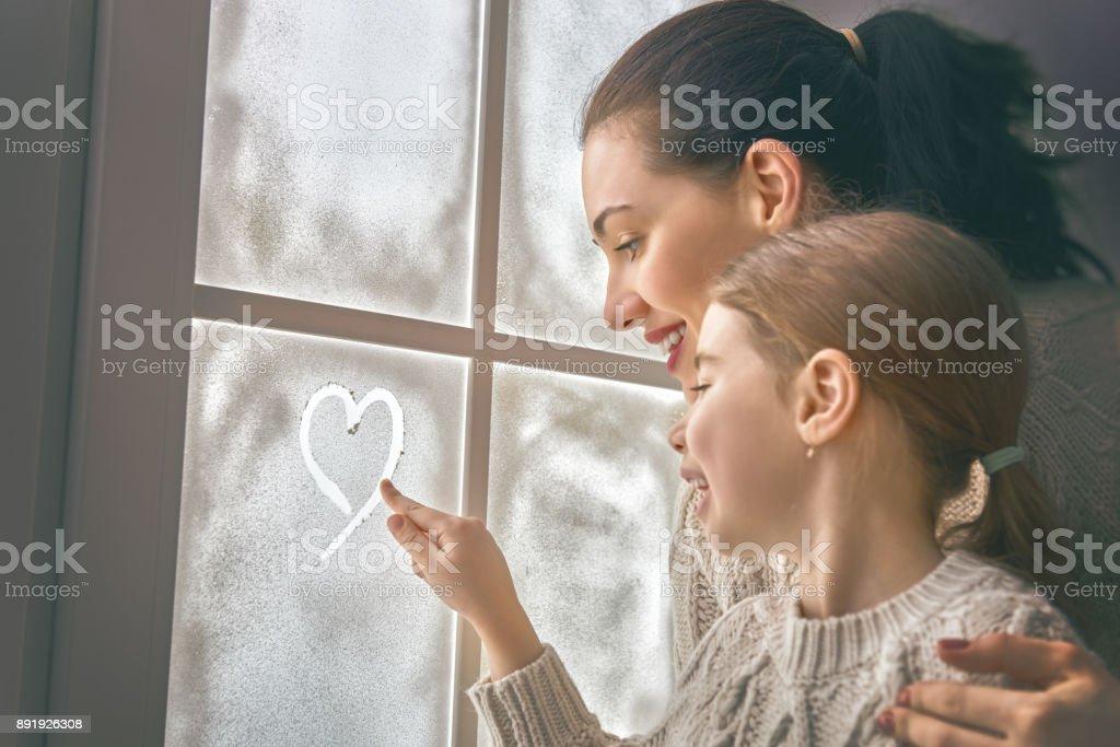 Familie zeichnen ein Herz auf gefrorenem Glas – Foto