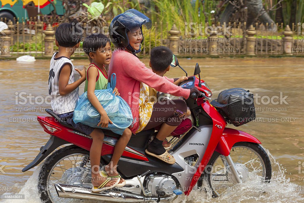 Family drives through floodwaters in Siem Reap, Cambodia stock photo