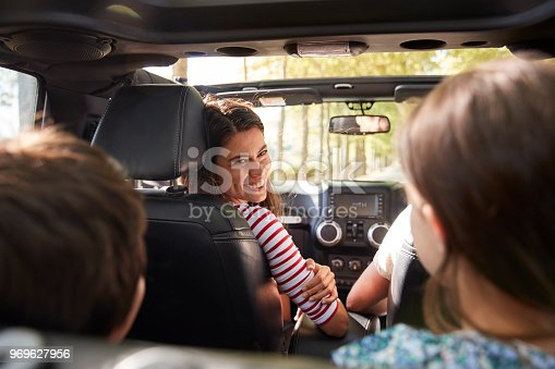 Family Driving In Open Top Car On Countryside Road Trip