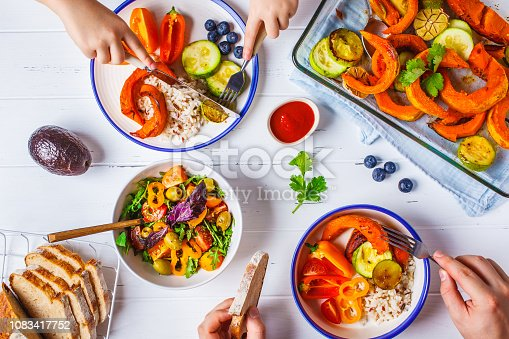 istock Family eating a healthy vegetarian food. Vegan lunch table top view, plant based diet. Baked vegetables, fresh salad, berries, bread on a white background. 1083417752