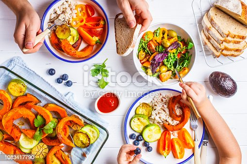 istock Family eating a healthy vegetarian food. Vegan lunch table top view, plant based diet. Baked vegetables, fresh salad, berries, bread on a white background. 1083417790