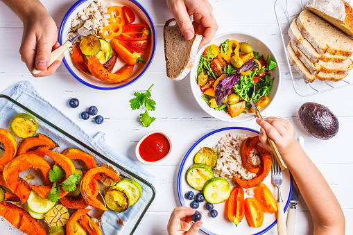 Flat lay of family hands eating healthy food. Vegan lunch table top view. Baked vegetables, fresh salad, berries, bread on a white background.