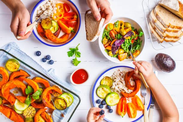 rodzina jedząca zdrowe wegetariańskie jedzenie. wegański lunch z widokiem na stół, dieta roślinna. pieczone warzywa, świeża sałatka, jagody, chleb na białym tle. - jedzenie wegetariańskie zdjęcia i obrazy z banku zdjęć
