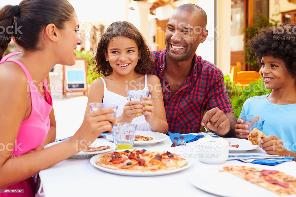 Family eating a meal at a outdoor restaurant together stock photo