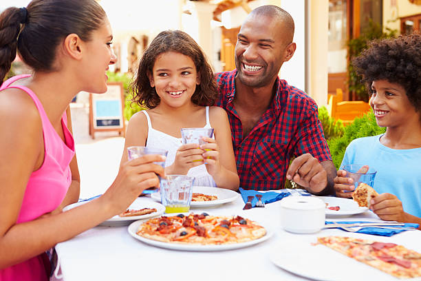 familia comiendo comida en el restaurante al aire libre junto - couple lunch outdoors fotografías e imágenes de stock