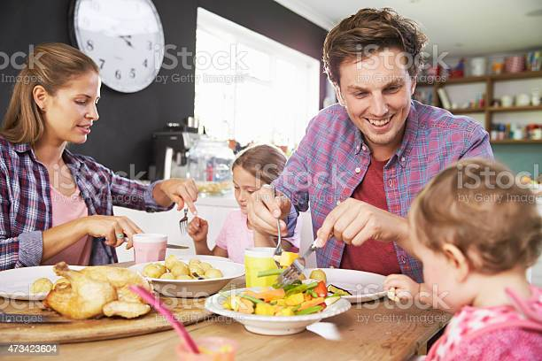 A Family Eating A Meal Together In The Kitchen Stock Photo - Download Image Now