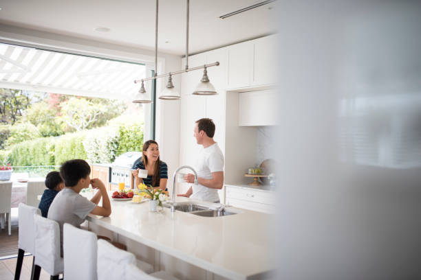 Family eating breakfast in the kitchen stock photo