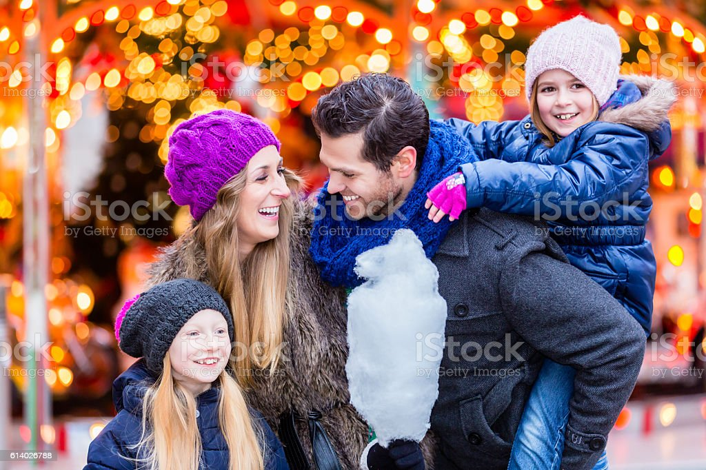 Family eating cotton candy on Christmas market - Photo