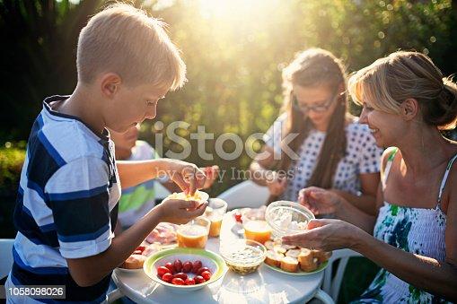 Three kids having fun eating fresh breakfast in the garden. Nikon D850