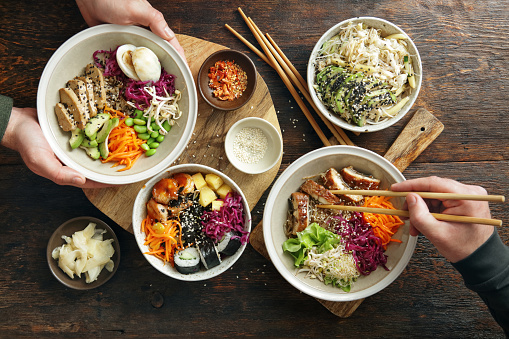 Family eating homemade poke noodle salad with unagi eel. Poke bowl with fried tofu, vegetables, carrot, edamame, cabbage, wakame, mango and spicy shrimps on a bed of brown rice. Glass noodle salad with avocado and mango. Flat lay top-down composition on wooden background.