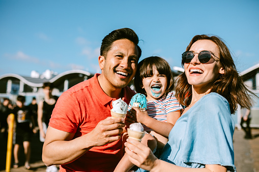 A portrait of a father, mother, and daughter enjoying ice cream cones at the Santa Monica Pier in Los Angeles, California.