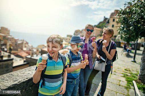 Family sightseeing Riomaggiore in Cinque Terre National Park - a UNESCO World Heritage Site. Everybody is having delicious italian gelato (ice cream) o a sunny spring day.  Nikon D850
