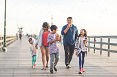 Two Filipino parents and their three children enjoy huge waffle ice cream cones on a California boardwalk by the beach. They are walking toward the camera. Mom is holding her youngest daughter's hand.
