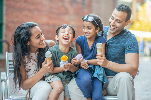 A mother, father, son and daughter are at an outdoor cafe. They are enjoying eating ice cream cones.