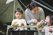 キャンプでマシュマロを食べる家族。