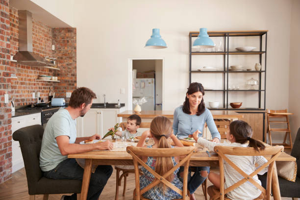 family eating meal in open plan kitchen together - family dinner stock photos and pictures