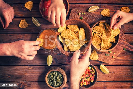 Family eating nachos with homemade sauces