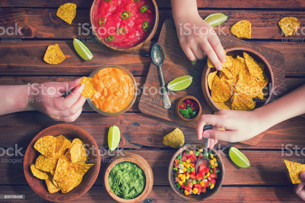 Family Eating Nachos With Sauces stock photo