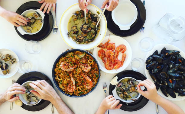Family eating Paella and seafood. Top view. stock photo