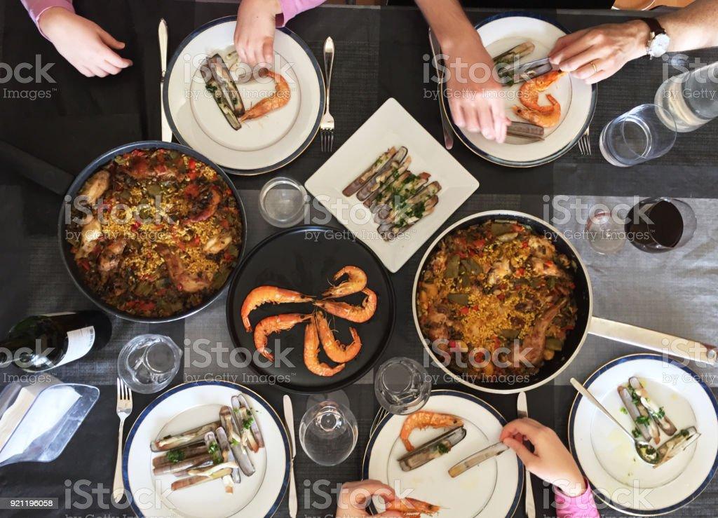 Família, comer Paella e frutos do mar. Vista superior. - foto de acervo