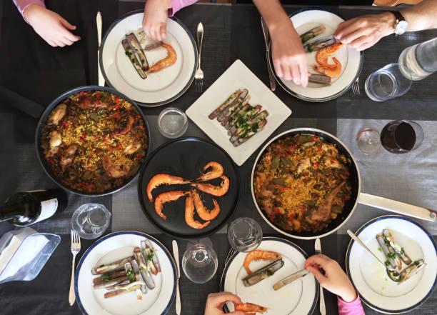 Famille manger Paella et fruits de mer. Vue de dessus. - Photo