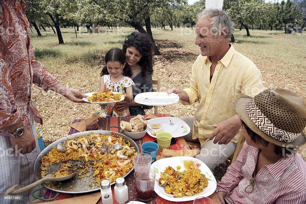 Famiglia mangiare paella all'aperto foto stock royalty-free