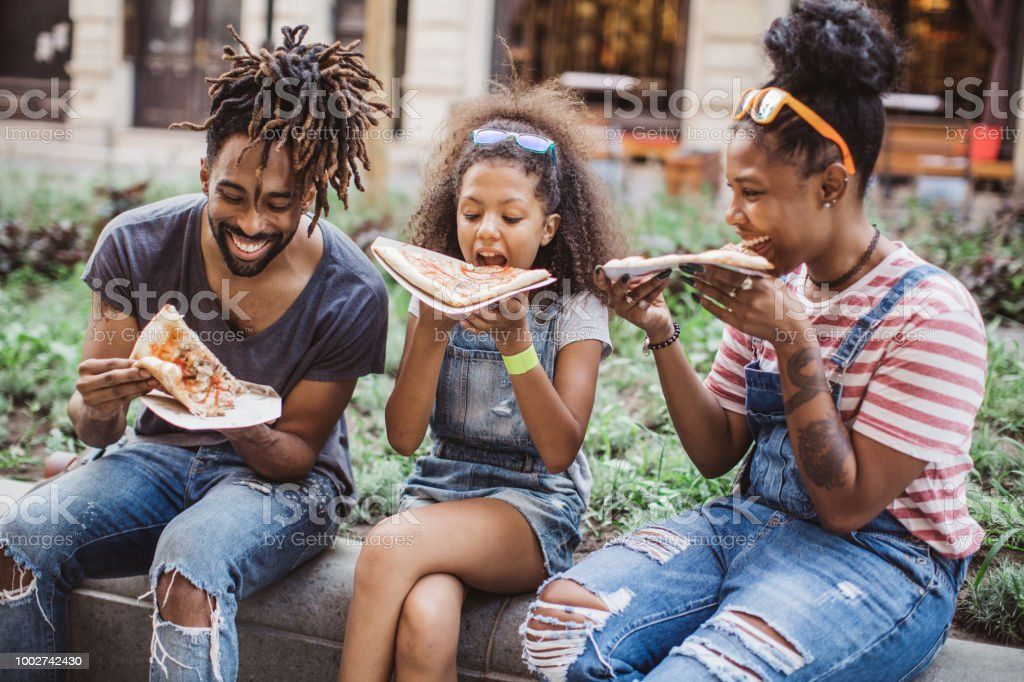 Family eating pizza on street stock photo