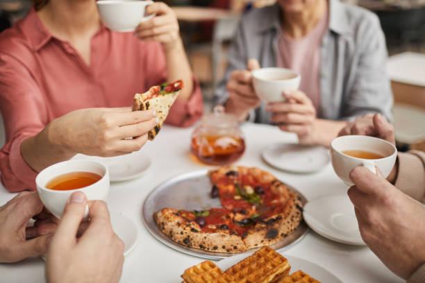 comer pizza en familia - happy couple sharing a cup of coffee fotografías e imágenes de stock