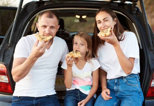 familia comiendo pizza juntos - couple lunch outdoors fotografías e imágenes de stock