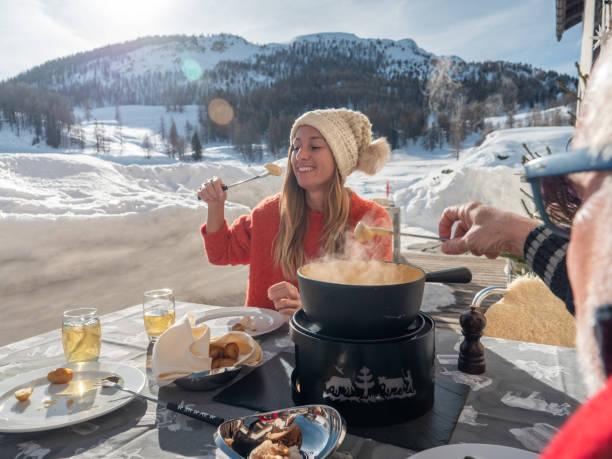 familie isst schweizer käsefondue in den alpen im winter - fondue stock-fotos und bilder