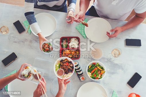 Family eating take out food at home. They are sitting at the dining table sharing Asian style food from take away containers with chopsticks. There is a variety of food on the table and some drinks and mobile phones. High angle view