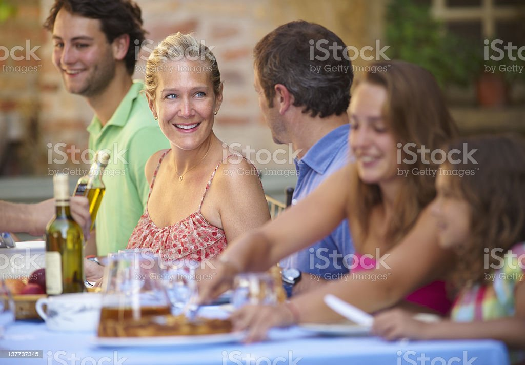 Family eating together outdoors stock photo