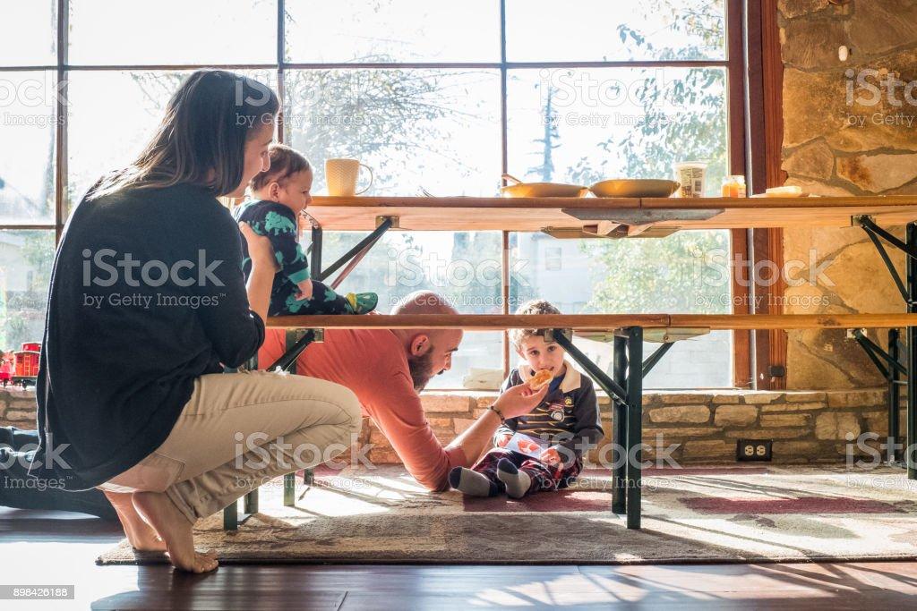 Family eats breakfast under the table stock photo