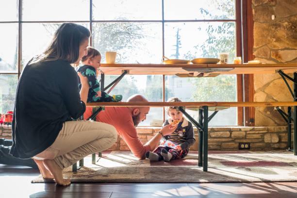家族がテーブルの下で朝食を食べる ストックフォト