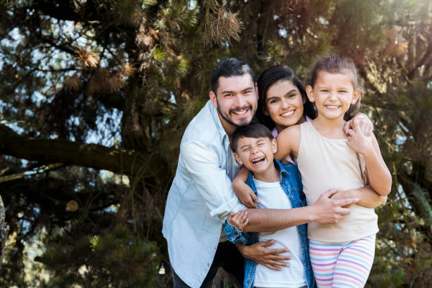 Family embraced in the garden Loving family, with dad and mom hugging their beautiful children in the garden of their house, while they look at the front and smile happily latin american culture stock pictures, royalty-free photos & images