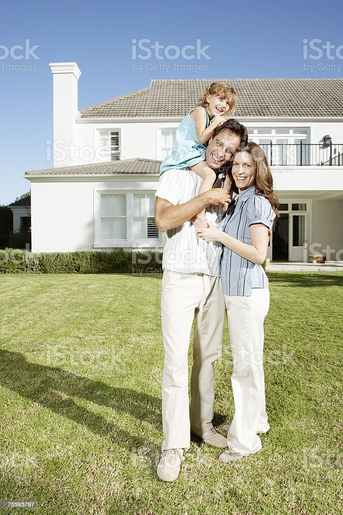 A family embracing in front of a large home royalty-free stock photo