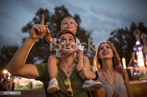 Family with one child outdoors on summer festival. Father carrying son on shoulders, they enjoy in festival entertaining
