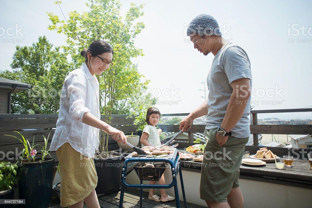 Family enjoying a barbecue on the terrace bildbanksfoto