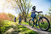 Mother and kids are enjoying a bike trip together during the COVID-19 pandemic.\nNikon D850