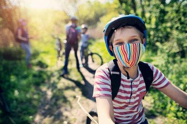 Family enjoying a bike trip during COVID-19 pandemic stock photo