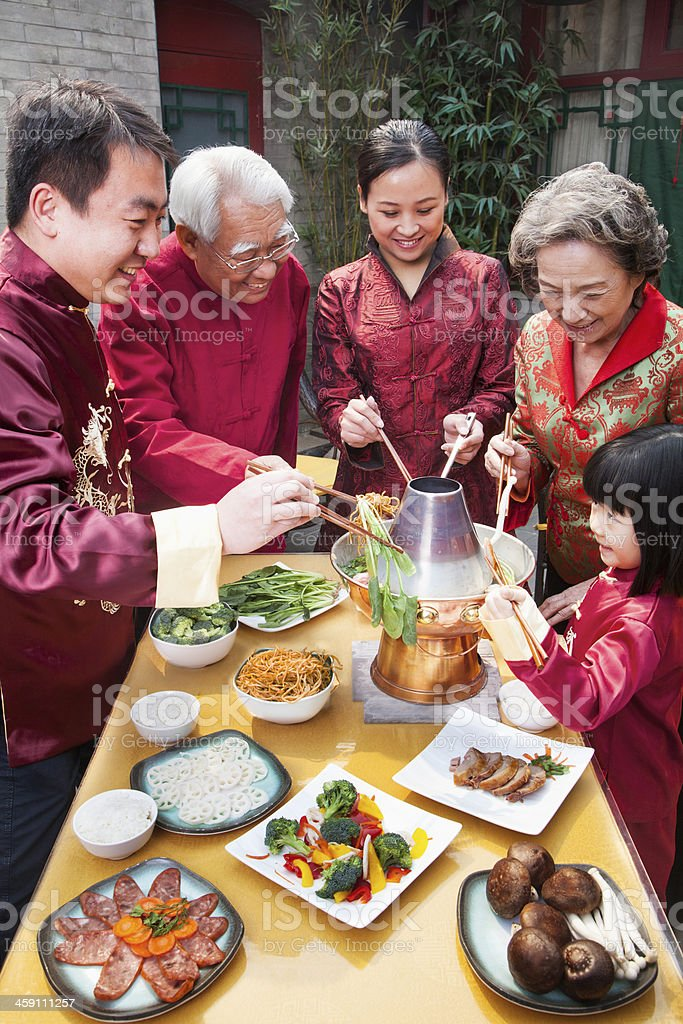 Family enjoying a traditional meal wearing Chinese clothing stock photo
