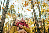 Little girl and her mother outdoors in autumn