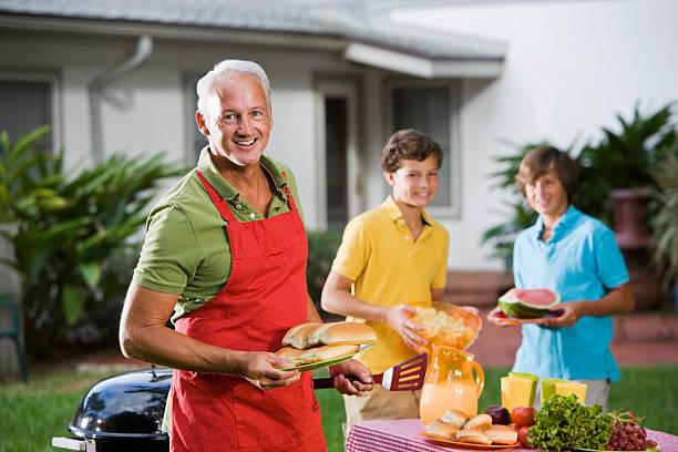 familien genießen picknick back yard - grillschürze stock-fotos und bilder