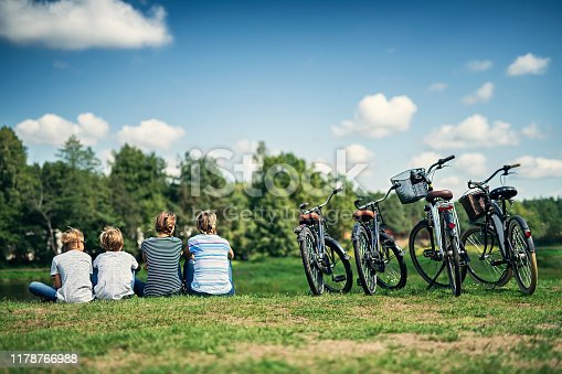 Family riding bicycles in nature. Mother and three kids are sitting in the grass and looking at the view. Nikon D850