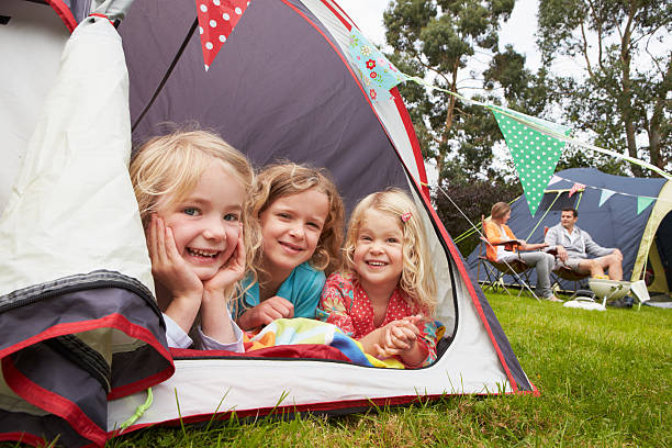 family enjoying camping holiday on campsite - camping stock photos and pictures
