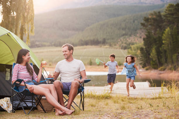 family enjoying camping vacation by lake together - camping stock photos and pictures