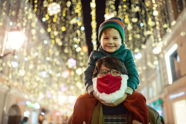 Family enjoying Christmas lights at a city street during COVID-19 pandemic